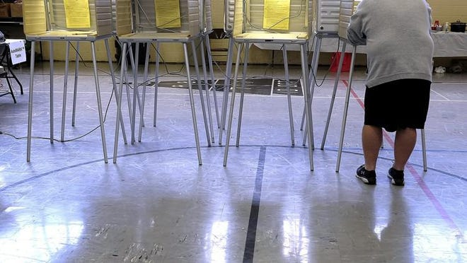 A man stand at a row of voting booths by himself as he votes at a Springfield election poll.