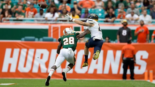Miami Hurricanes defensive back Michael Jackson (28) breaks up a pass intended for Toledo Rockets wide receiver Cody Thompson (25) at Hard Rock Stadium in Miami Gardens, Florida on September 23, 2017.