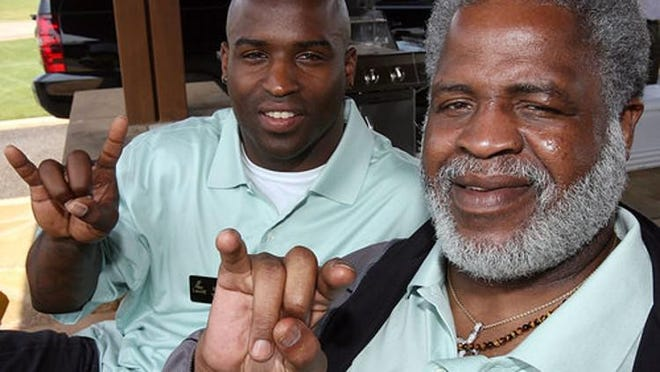 Ricky Williams and Earl Campbell pose with a Hook 'Em sign during a 2008 celebrity golf tournament held in Spicewood. (AMERICAN-STATESMAN FILE PHOTO]