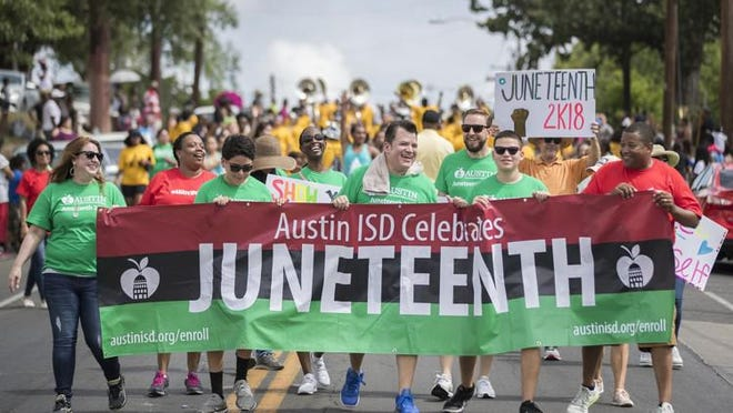Austin students and staff walk in a Juneteenth parade in Austin on June 16, 2018.