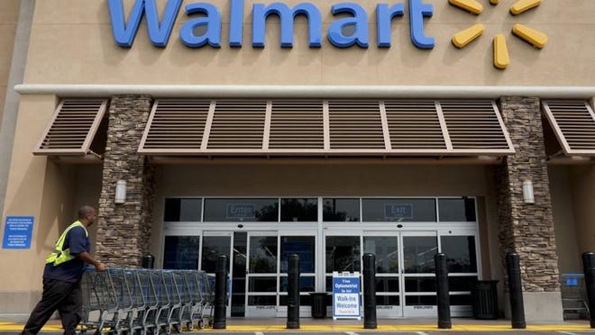 FILE - In this May 9, 2013, file photo, a worker pushes shopping carts in front of a Walmart store.