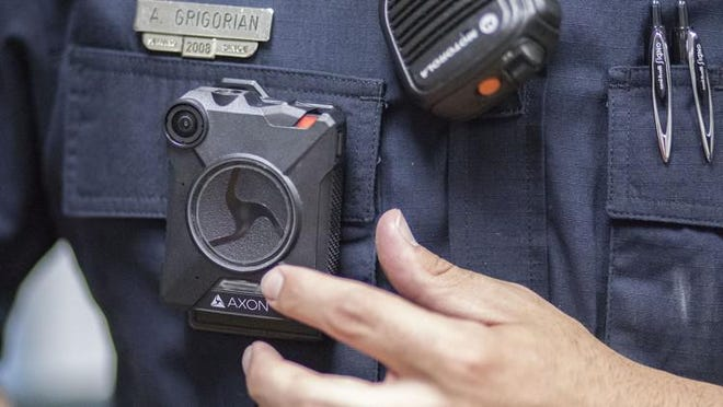 An officer demonstrates an Axon body camera in this USA Today Network file photo.