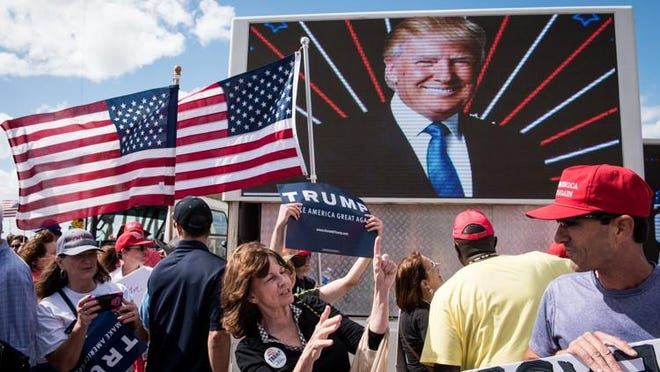 Trump supporters rally together on Southern Boulevard in the Palm Beach side of the Bingham Island bridge on Saturday, Mar. 4, 2017. The president?s motorcade passed through with Trump stepping out of his vehicle to wave to his supporters before continuing on in the direction toward Mar-a-Lago.