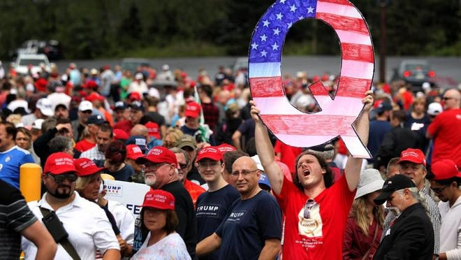 WILKES BARRE, Pa. ? David Reinert holds up a large ?Q? sign while waiting in line to see President Donald J. Trump at his rally on August 2, 2018 at the Mohegan Sun Arena at Casey Plaza in Wilkes Barre, Pennsylvania. ?Q? represents QAnon, a conspiracy theory group that has been seen at recent rallies.