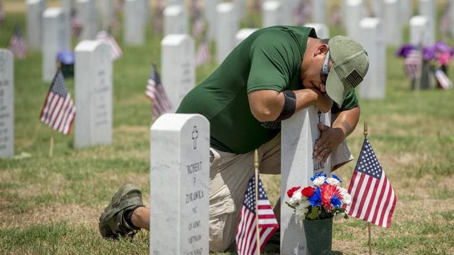Army veteran Tony Alaniz of Killeen, Tex., visits the grave of his son, Joseph Alaniz, on Memorial Day at the Central Texas State Veterans Cemetery in Killeen in 2018. Georgia legislation was scheduled for discussion Tuesday to place a state veterans' cemetery in Augusta.