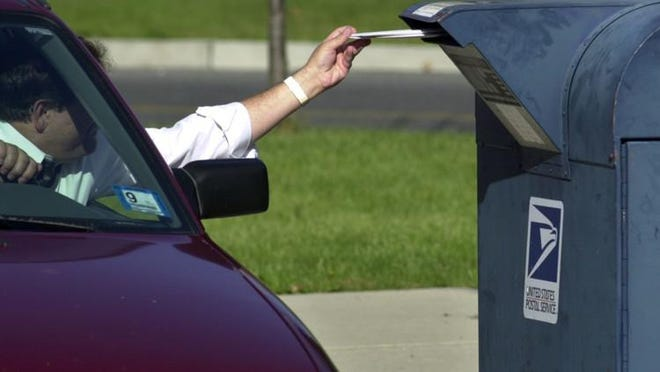 A postal customer drops mail into a drive by mailbox.