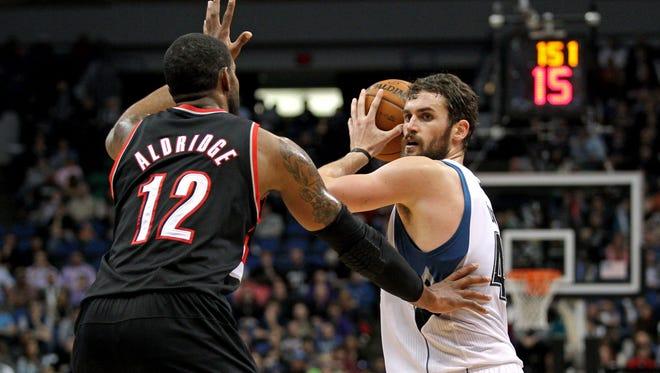 Timberwolves forward Kevin Love looks to pass around Blazers forward LaMarcus Aldridge during Minnesota's win.