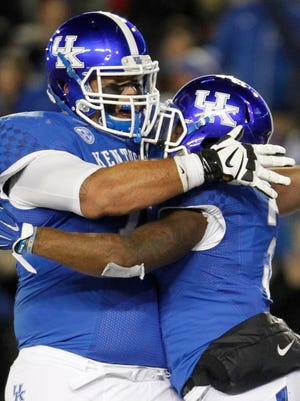 Kentucky Wildcats running back Jojo Kemp (3) and offensive guard Cole Mosier (74) celebrate in the endzone during the game against the Charlotte 49ers in the first hafl at Commonwealth Stadium.