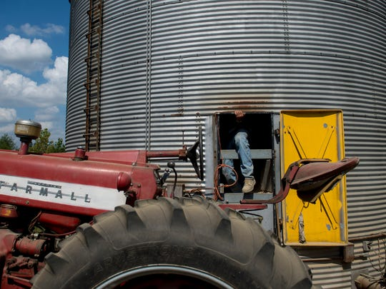 Donald Temme climbs out of a grain bin that stores