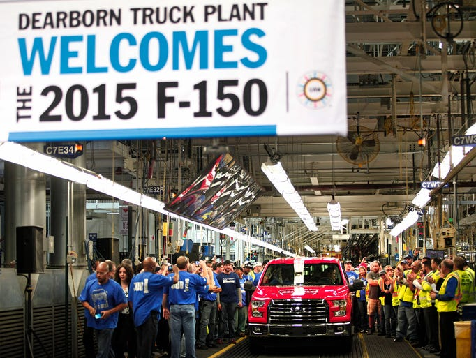 Autoworkers applaud and take photos of the  first