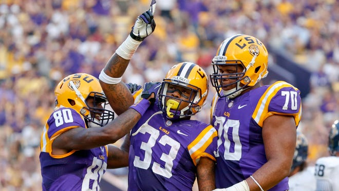 LSU Tigers running back Jeremy Hill (33) celebrates a touchdown with wide receiver Jarvis Landry (80) and offensive tackle La'el Collins (70) during the first half of a game against the Kent State Golden Flashes at Tiger Stadium.