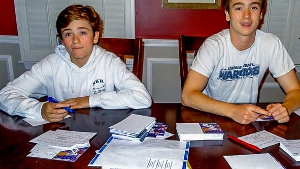 Ollie Reinhardt, left, and his older brother, Max, are almost done writing their 400 postcards.