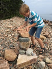 Max Burkett stacks a cairn on a beach in Ship Harbor