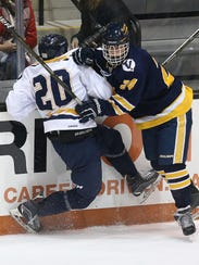Matthew Stuewe (20) is checked along the boards by