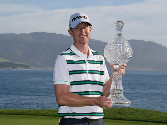 Vaughn Taylor poses with his trophy on the 18th green