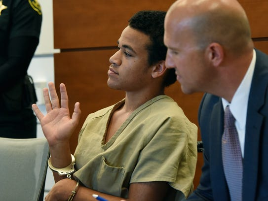 Zachary Cruz, left, gestures to the judge while seated