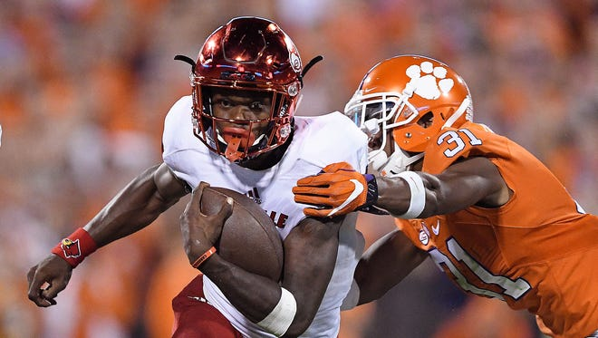 Lamar Jackson of the Louisville Cardinals looks to avoid the tackle of Ryan Carter of the Clemson Tigers during the fourth quarter at Memorial Stadium on Oct. 1, 2016 in Clemson, South Carolina.