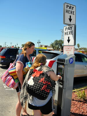 Students from the University of Maryland on Spring Break pay to park at a kiosk in a downtown Cocoa Beach parking lot.  The city is working on additional plans for parking.