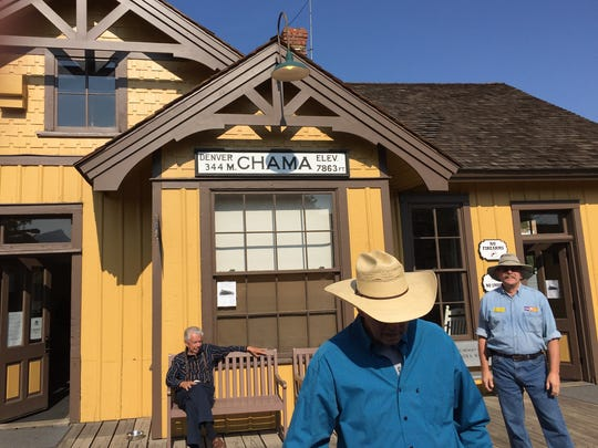 People take a break at the Chama train depot before