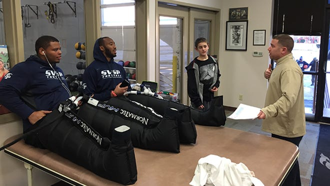 "Sports agent Andrew ""Buddy"" Baker talks with Deon Simon, left, and Obum Gwacham at St. Vincent Sports Performance in Indianapolis. They're wearing compression boots to promote muscle recovery. Baker's son Braden is also in the photo."