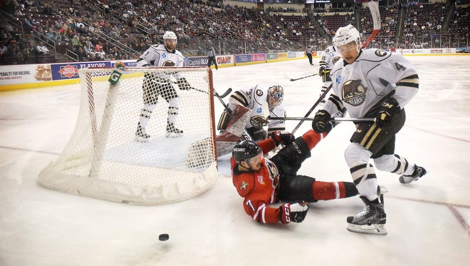 Portland Pirate Wayne Simpson (7) goes down in front of Hershey Bear Madison Bowey (4) behind the Hershey goal while battling for the puck in the first period of play Sunday, May 1, 2016, at the Giant Center in Hershey.