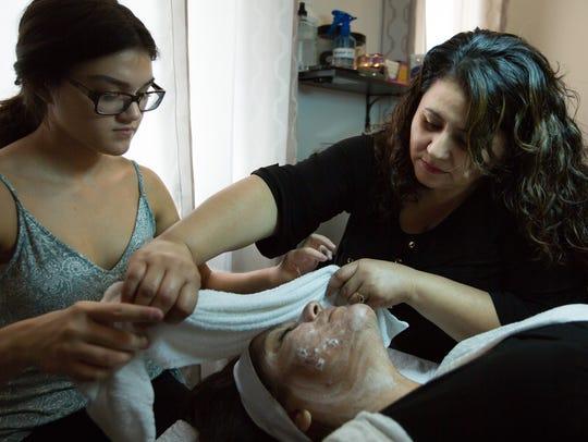 Glitz esthetician instructor Martha Mata, right, assists