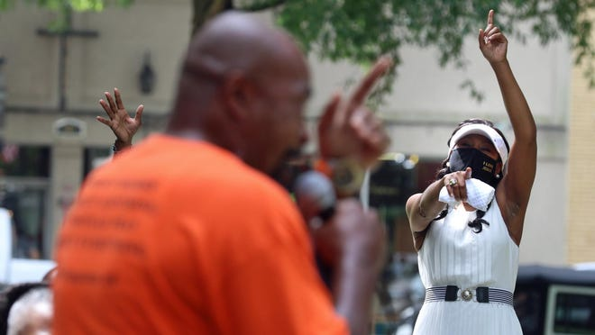 Pastor Trecia Haynes raises her hand in praise as she and others listen to the Rev. Herman Chalk speak during the Unity In The Community event held Saturday outside the Earl Scruggs Center in Shelby.