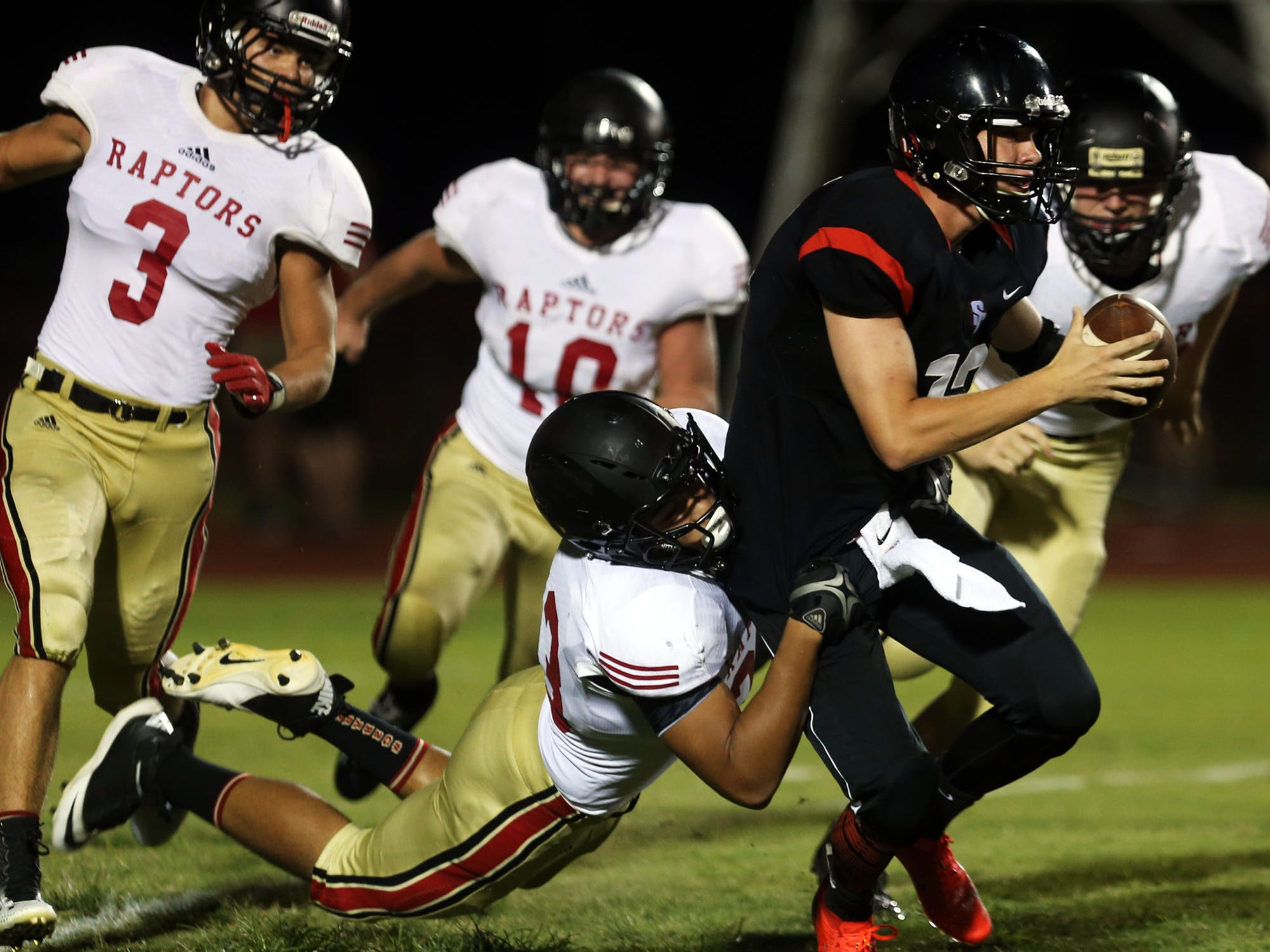 Stewarts Creek quarterback Mason Hall is sacked by Ravenwood's Bryan McKay in the second quarter Friday, August 22, 2014 at Stewarts Creek.