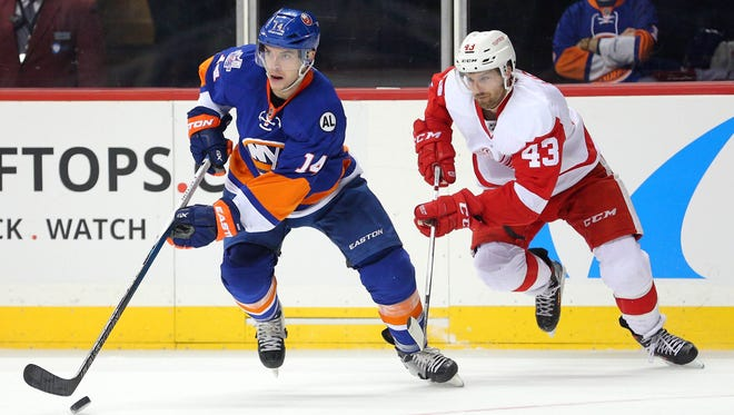 Feb 15, 2016; Brooklyn, NY, USA; New York Islanders defenseman Thomas Hickey (14) controls the puck in front of Detroit Red Wings center Darren Helm (43) during the second period at Barclays Center.