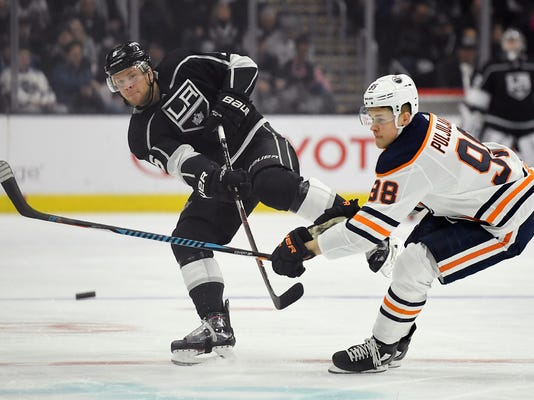 Los Angeles Kings defenseman Christian Folin, left, of Sweden, passes the puck while under pressure from Edmonton Oilers right wing Jesse Puljujarvi, of Sweden, during the second period of an NHL hockey game, Saturday, Feb. 24, 2018, in Los Angeles. (AP Photo/Mark J. Terrill)