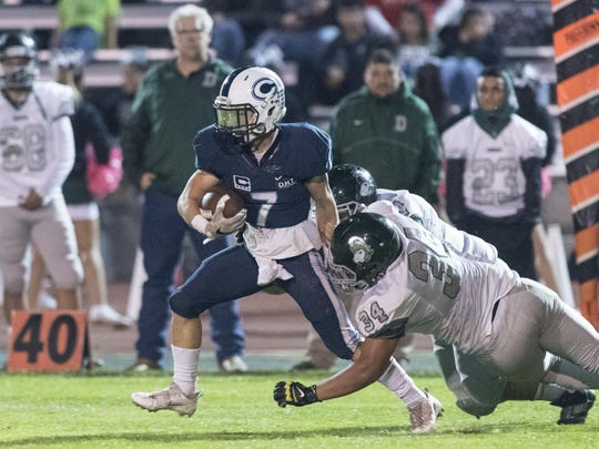 Central Valley Christian's Connor Paden runs away from Dinuba's Josh Sanchez and Jose Guido in a Central Sequoia League football game on Friday, October 28, 2016.