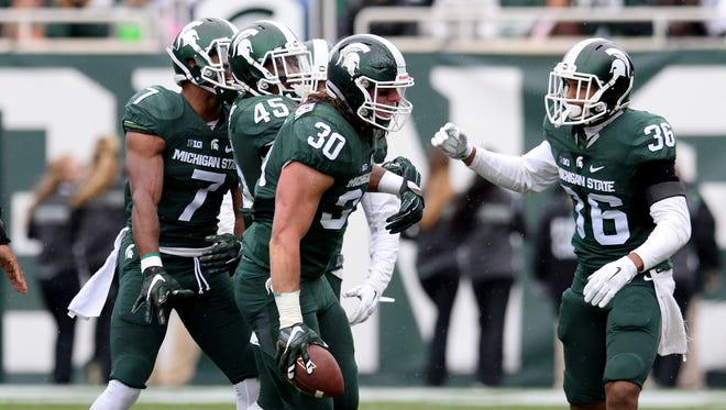 MSU linebacker Riley Bullough, center, celebrates with teammates after coming up with a fumble against Purdue               at Spartan Stadium Saturday 10/3/2015.