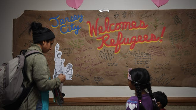 Roli Rastogi, left, a volunteer with JC Moms, writing a welcome message on a poster during Friendship Day at the Church of Jesus Christ of Latter Day Saints in Jersey City on Saturday.