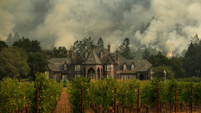A wildfire burns behind a winery Saturday in Santa Rosa.