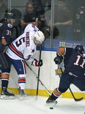 File Photo: Oklahoma's Bogdan Yakimov reaches for the puck as Amerks's Chad Ruhwedel blocks his stick with his body while the puck sits behind Oklahoma's Matthew Ford in the first period at the Blue Cross Arena at the War Memorial in Rochester.