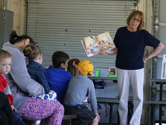 Terri Winke, preschool coordinator for Ida Rupp Public Library, reads a cleanup-themed children's book during 'Nature Story Time' at Lakeview Park on Tuesday.
