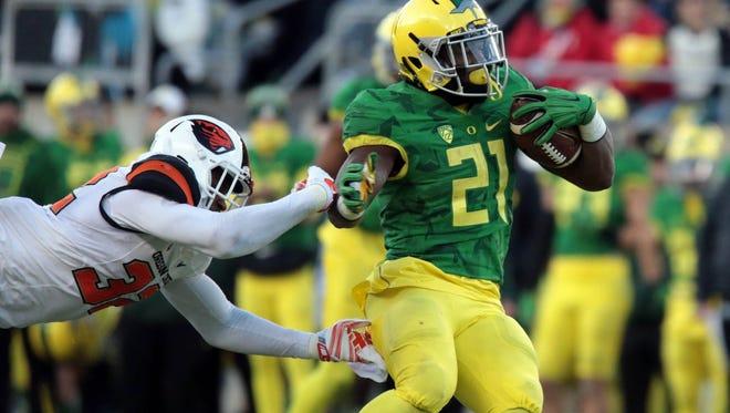 Oregon running back Royce Freeman (21) is pursued by Oregon State linebacker Jonathan Willis during the 2015 Civil War at Autzen Stadium in Eugene.