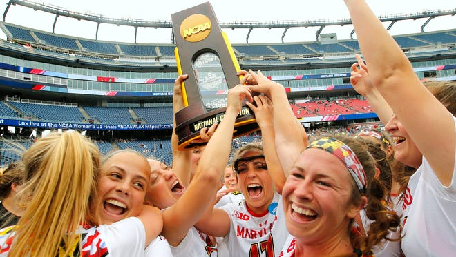 Maryland attack Caroline Wannen holds up the trophy with help from attack Megan Whittle as midfielder Zoe Stuckenberg gets a hug from a teammate after their 16-13 win over Boston College in the NCAA Championship game.