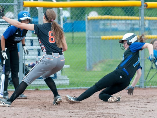 Lindsay Clark (7) from Harper Creek, slides into home