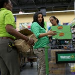 Walmart employees Iliana Sanchez, left, and Maria Macias stock the shelves at a Walmart store on Feb. 19 in Miami.