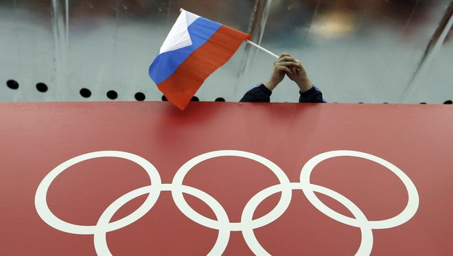 In this Feb. 18, 2014 file photo, a Russian skating fan holds the country's national flag over the Olympic rings before the start of the men's 10,000-meter speedskating race at Adler Arena Skating Center during the 2014 Winter Olympics in Sochi.