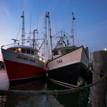 Fishing boats sit docked along Manasquan Inlet in Point