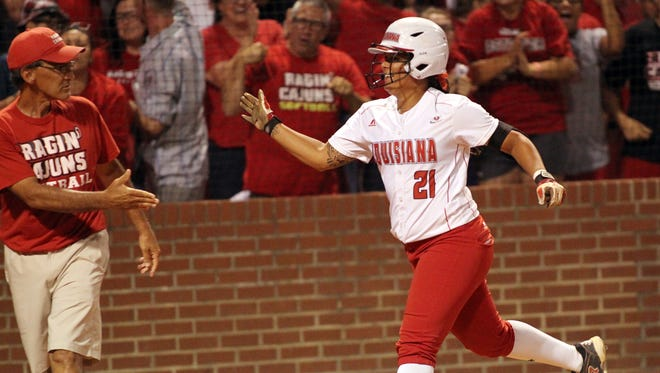 UL's Samantha Walsh prepares to shake head coach's Michael Lotief's hand after hitting a two-run home run in the Ragin' Cajuns' 5-3 win over Arizona in Game 1 of the NCAA Super Regional.