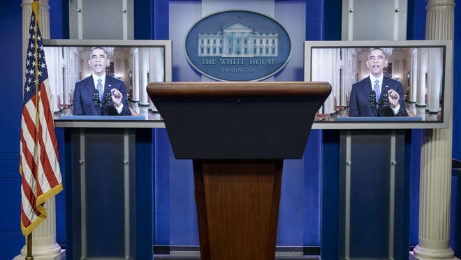 President Obama is seen on screens in the White House briefing room during a televised address to the nation.