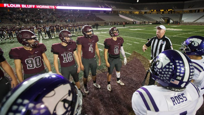 Flour Bluff captions meet for the coin flip before their Class 5A Division I regional semifinal game against Angleton Friday, Dec. 1, 2017, at Bobcat Stadium in San Marcus.