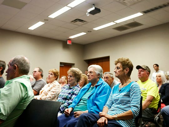 Citizens listen during a meeting regarding the former