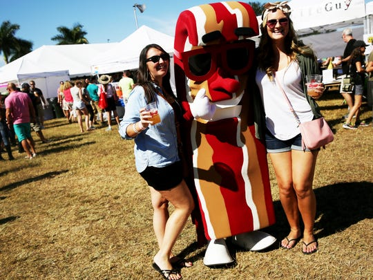 Megan Griffis of Lehigh Acres, right, and Marie Cimirro of Naples take a photo with a bacon character during Bacon Fest at the Naples Airport on Saturday, Nov. 12, 2016.
