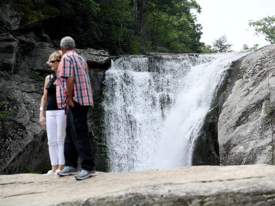People stand on the rocks below Elk River Falls in the Pisgah National Forest July 20, 2018.