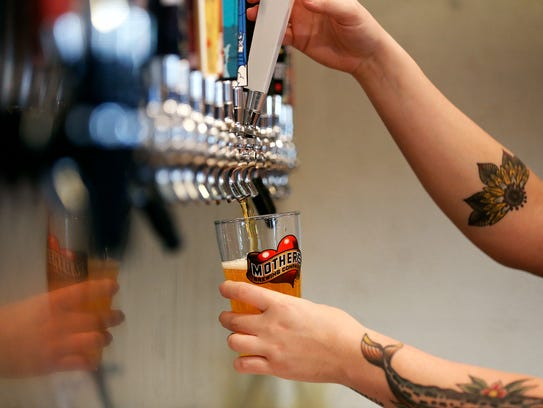 Anne Mauldin pours a beer at the Mother's Brewing Company