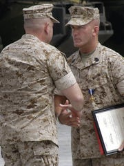 Marine Sgt. Maj. Brad Kasal, right, received the Navy Cross during a ceremony in May 2006 at Camp Pendleton, Calif. Kasal, 39, who grew up on a farm near Afton, Iowa, also was promoted and re-enlisted.